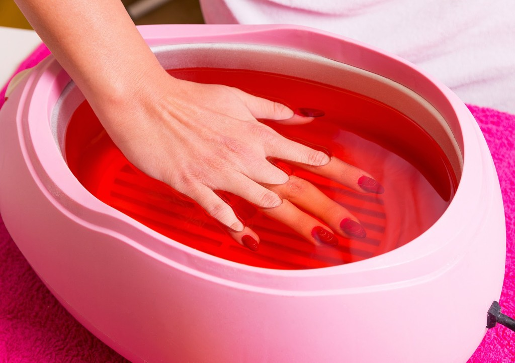Female hand and orange paraffin wax in bowl. Manicure and skincare. Woman girl in beauty spa salon.